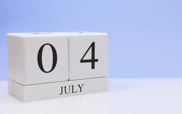 4 juli. dag 4 van de maand, dagelijkse kalender op witte tafel met reflectie, met lichtblauwe achtergrond Premium Foto
