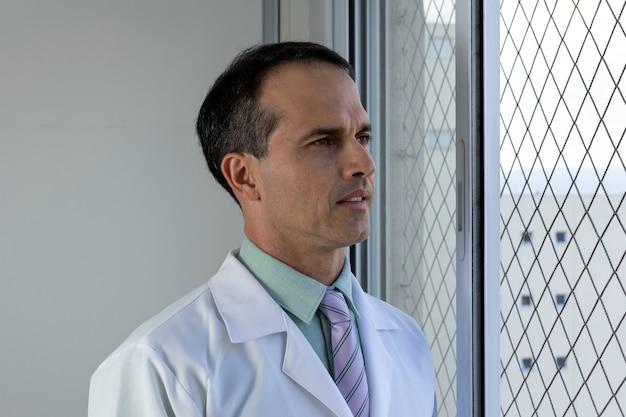 44 jaar oude dokter met witte jas en stropdas die naar het raam kijkt. Premium Foto