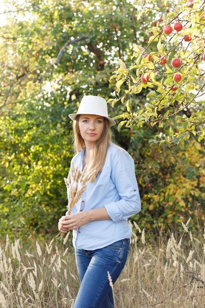 45-jarige vrouw in een blauw shirt en hoed poseren in een appelboomgaard Premium Foto