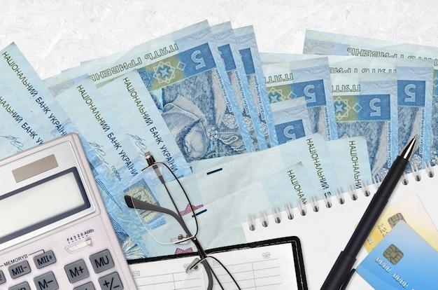 5 oekraïense hryvniasrekeningen en rekenmachine met bril en pen. Premium Foto