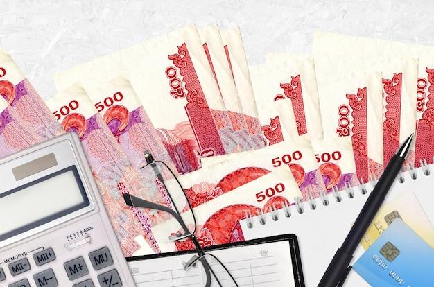 500 cambodjaanse riels-rekeningen en rekenmachine met bril en pen. Premium Foto