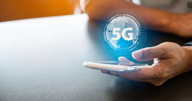 5g netwerk digitaal hologram en internet van dingen. 5g netwerk draadloze systemen. close-up van mannenhand typen bericht op mobiele smartphone. Premium Foto