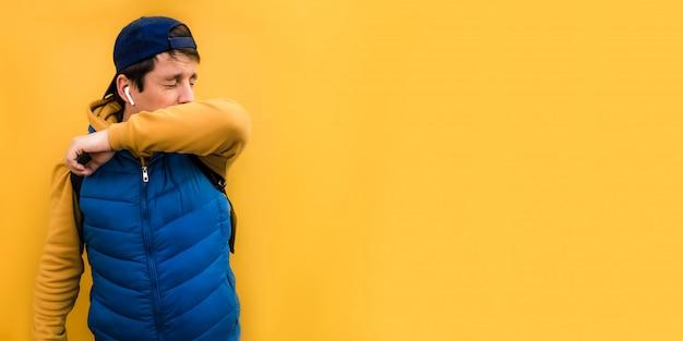 6x3 banner europese man met blauwe kleren aan niest in zijn elleboog van het virus en sluit zijn ogen. het concept van niezen op een gele achtergrond copyspace. Premium Foto