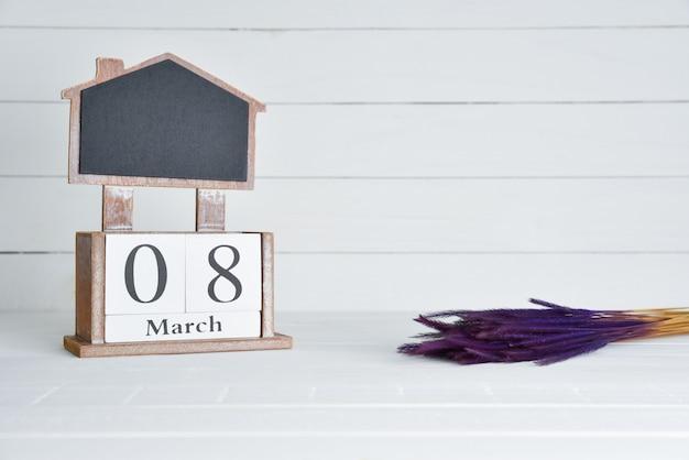 8 maart houten het blokkalender van de tekst met purpere droge bloem op witte houten achtergrond. Premium Foto