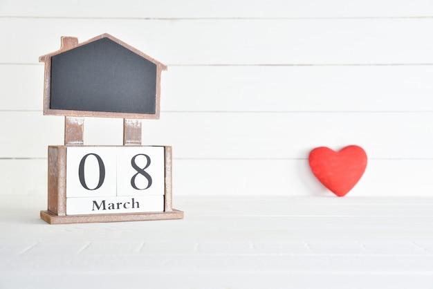 8 maart houten het blokkalender van de tekst met rood hart op witte houten achtergrond. Premium Foto