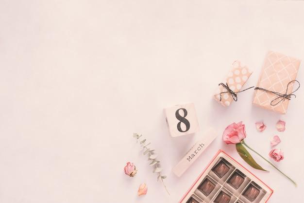 8 maart inscriptie met bloemen, geschenken en chocoladesnoepjes Gratis Foto
