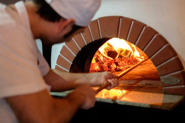 à â¡hef bereidt pizza in traditionele steenoven. Premium Foto