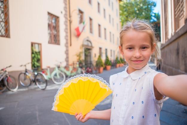 Aanbiddelijk gelukkig meisje die selfie in openlucht in europese stad nemen. het portret van kaukasisch jong geitje geniet de zomer van vakantie in oude stad Premium Foto