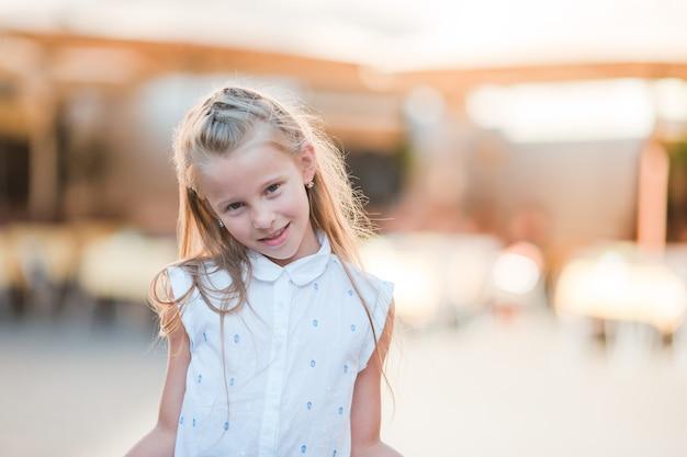 Aanbiddelijk gelukkig meisje in openlucht in italiaanse stad. Premium Foto