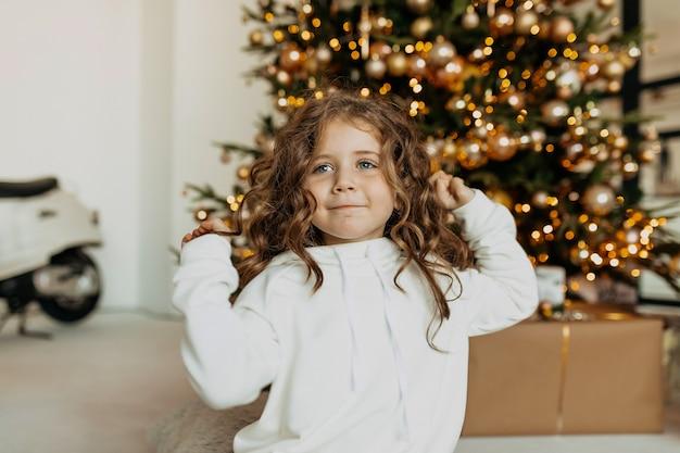 Aanbiddelijk grappig meisje gekleed witte kleren die pret voor kerstboom hebben Gratis Foto
