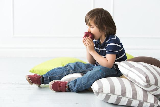 Aanbiddelijk jong geitje dat op de vloer appel eet Gratis Foto