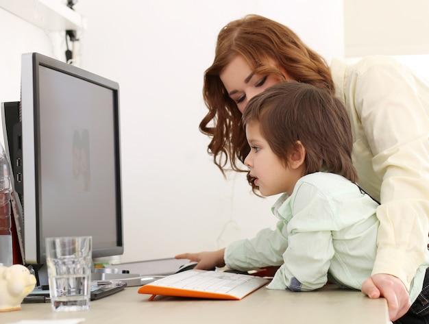 Aanbiddelijk jong geitje en moeder die een computer met behulp van Gratis Foto