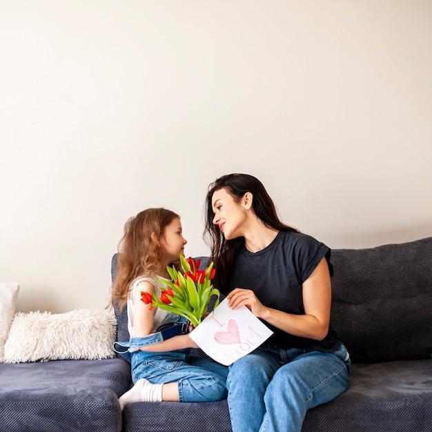 Aanbiddelijk jong meisje dat bloemen geeft aan haar moeder Gratis Foto