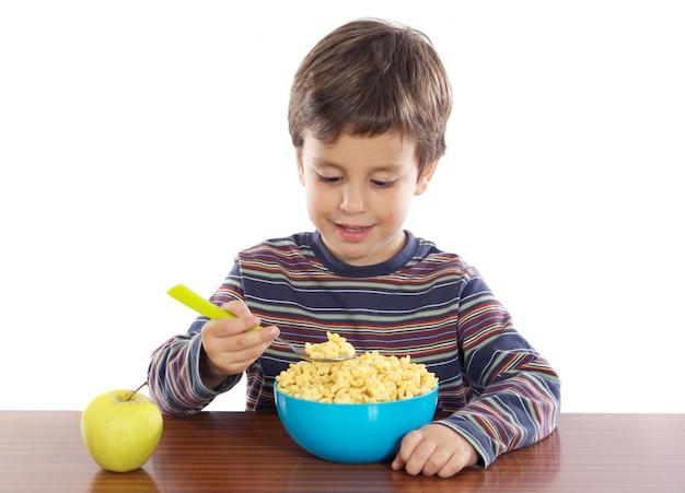 Aanbiddelijk kind dat a over witte achtergrond ontbijt Premium Foto
