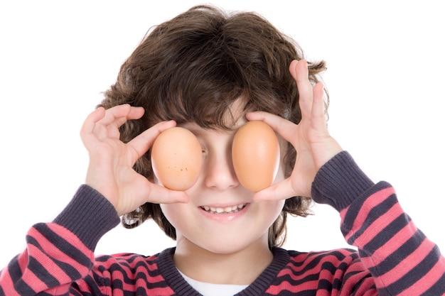 Aanbiddelijk kind met twee eieren op zijn ogen op een witte achtergrond Premium Foto