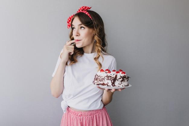 Aanbiddelijk krullend meisje dat aardbeientaart proeft. binnen schot van romantisch vrouwelijk model met rood lint in haar die smakelijke pastei houden. Gratis Foto