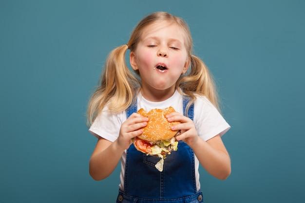 Aanbiddelijk leuk meisje in wit overhemd en jean jumpsuit met hamburger Premium Foto