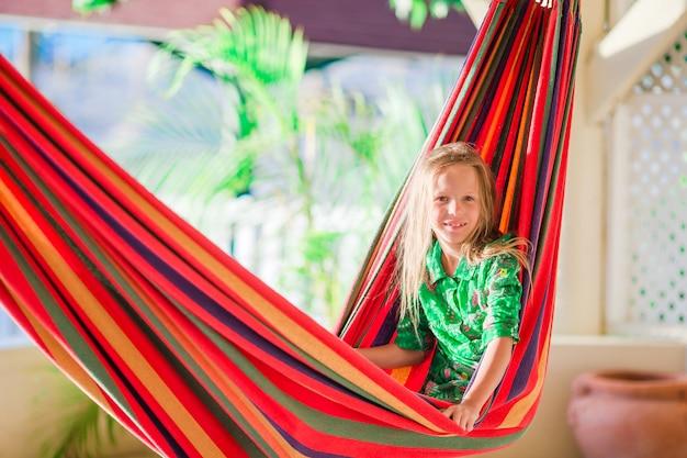 Aanbiddelijk meisje bij het tropische vakantie ontspannen in hangmat Premium Foto