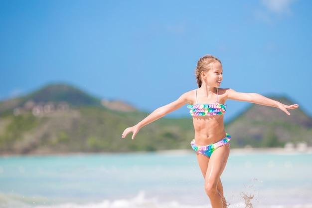 Aanbiddelijk meisje bij strand dat heel wat pret in ondiep water heeft Premium Foto