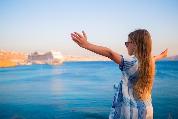 Aanbiddelijk meisje bij strand grote lainer als achtergrond in griekenland Premium Foto