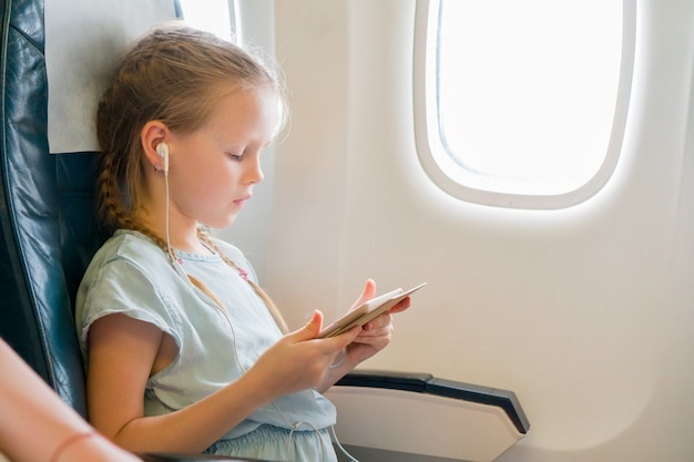 Aanbiddelijk meisje dat door een vliegtuig reist. leuk jong geitje met laptop dichtbij venster in vliegtuigen Premium Foto