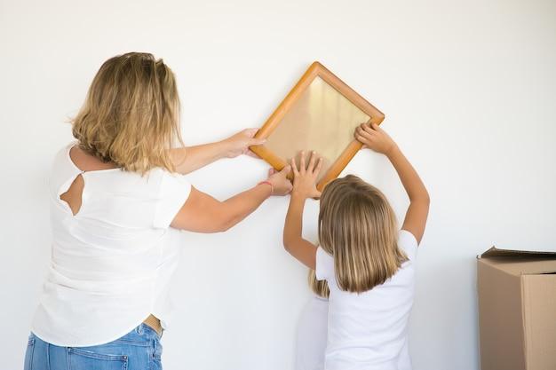 Aanbiddelijk meisje dat fotokader op witte muur met hulp van mamma zet Gratis Foto