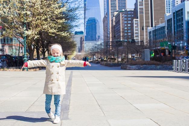 Aanbiddelijk meisje dat in de stad van new york bij de lente zonnige dag loopt Premium Foto