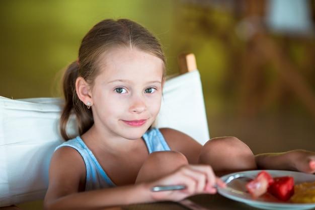 Aanbiddelijk meisje dat lunch in openluchtkoffie heeft Premium Foto