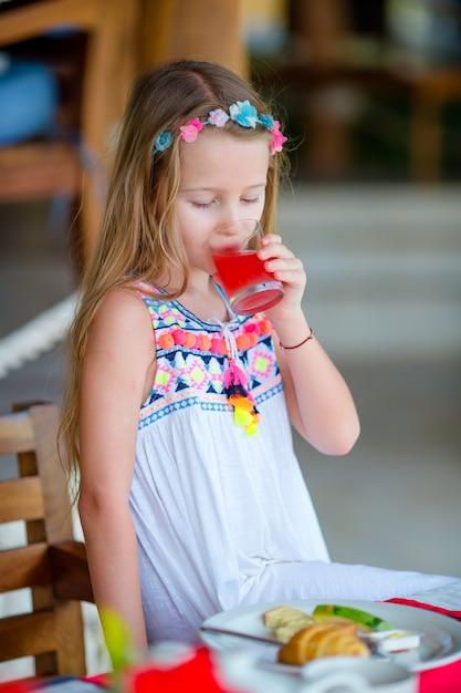 Aanbiddelijk meisje dat ontbijt heeft bij openluchtkoffie. deksel druppelt vers sap Premium Foto
