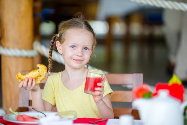 Aanbiddelijk meisje dat ontbijt heeft bij openluchtkoffie Premium Foto