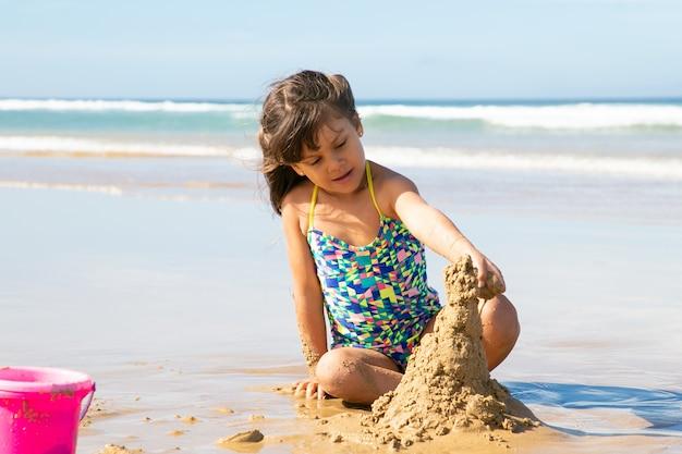 Aanbiddelijk meisje dat zandkasteel bouwt op strand, zittend op nat zand, genietend van vakantie door oceaan Gratis Foto
