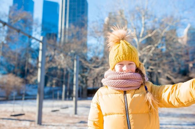 Aanbiddelijk meisje die selfie foto in central park bij de stad van new york nemen Premium Foto