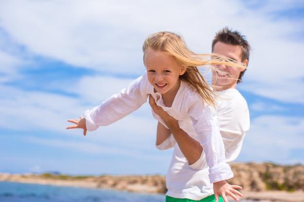 Aanbiddelijk meisje en gelukkige vader tijdens strandvakantie Premium Foto