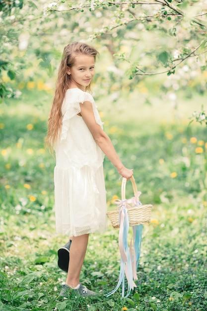 Aanbiddelijk meisje in bloeiende appeltuin op mooie de lentedag Premium Foto