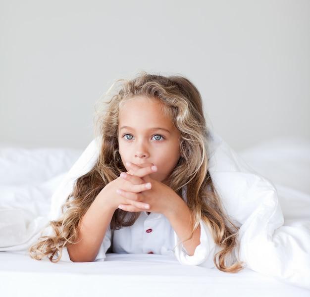 Aanbiddelijk meisje in een bed Premium Foto