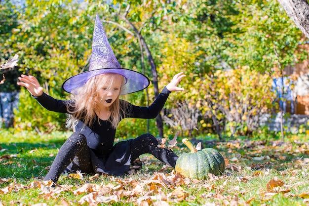 Aanbiddelijk meisje in halloween welk kostuum dat pret heeft in openlucht Premium Foto