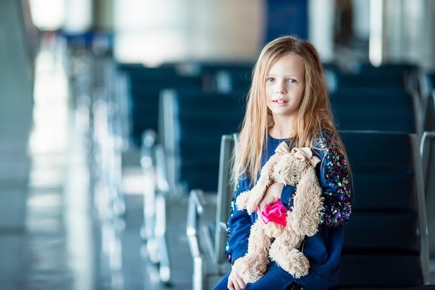 Aanbiddelijk meisje in luchthaven binnen alvorens in te schepen Premium Foto