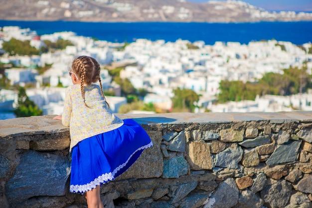 Aanbiddelijk meisje in mykonos-stads verbazend mening als achtergrond van traditionele witte huizen Premium Foto