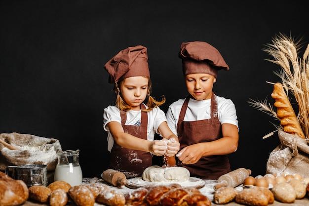 Aanbiddelijk meisje met broer het koken Premium Foto
