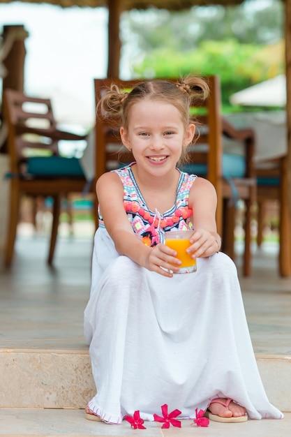 Aanbiddelijk meisje met sap bij openluchtkoffie Premium Foto
