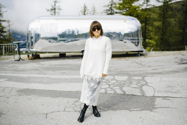 Aanbiddelijk meisje op hoge bergweg dichtbij aan de auto Gratis Foto