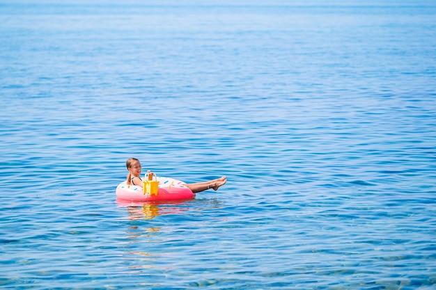 Aanbiddelijk meisje op opblaasbaar luchtbed in de zee Premium Foto