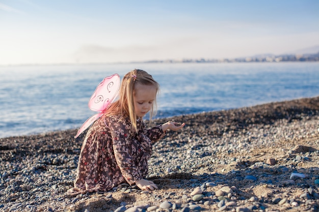 Aanbiddelijk meisje spelen op het strand in een zonnige winterdag Premium Foto