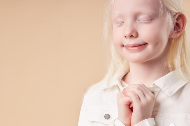 Aanbiddelijk mooi kindmeisje met witte haarkleur en huidtribune met gesloten ogen Premium Foto