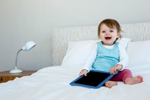 Aanbiddelijke baby die een tablet houdt en op een bed zit Premium Foto
