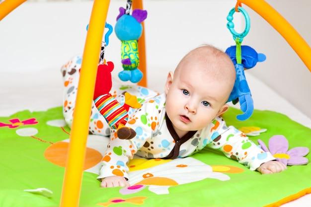 Aanbiddelijke baby die pret met speelgoed op kleurrijke speelmat heeft. Premium Foto