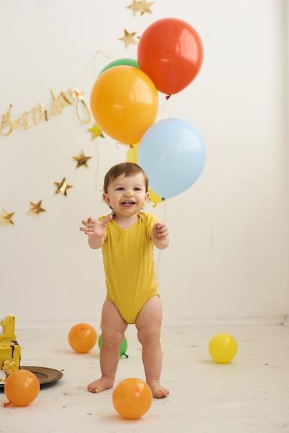 Aanbiddelijke babyjongen die geel lichaam draagt en een kleine verjaardagstaart eet. Premium Foto