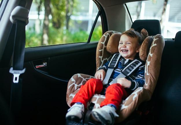 Aanbiddelijke babyjongen in een veiligheidsautozetel. Premium Foto
