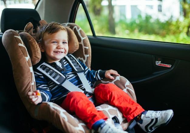 Aanbiddelijke babyjongen in veiligheidsautozetel. Premium Foto
