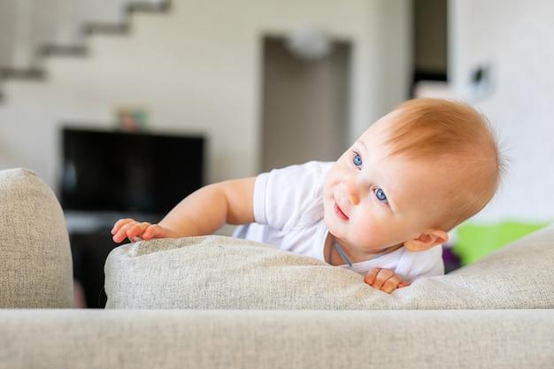 Aanbiddelijke babyjongen in witte zonnige slaapkamer. het pasgeboren kind ontspannen op een blauw bed. kinderkamer voor jonge kinderen. Premium Foto